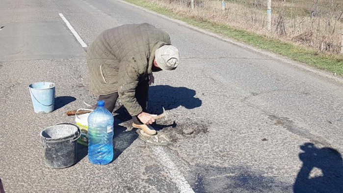 Дядо кърпи дупките по пътя между две села